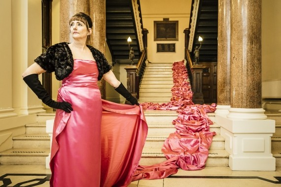 Giovanna Maria Casetta at SPILL Festival, comind down a grandiose staircase in a long pink dress