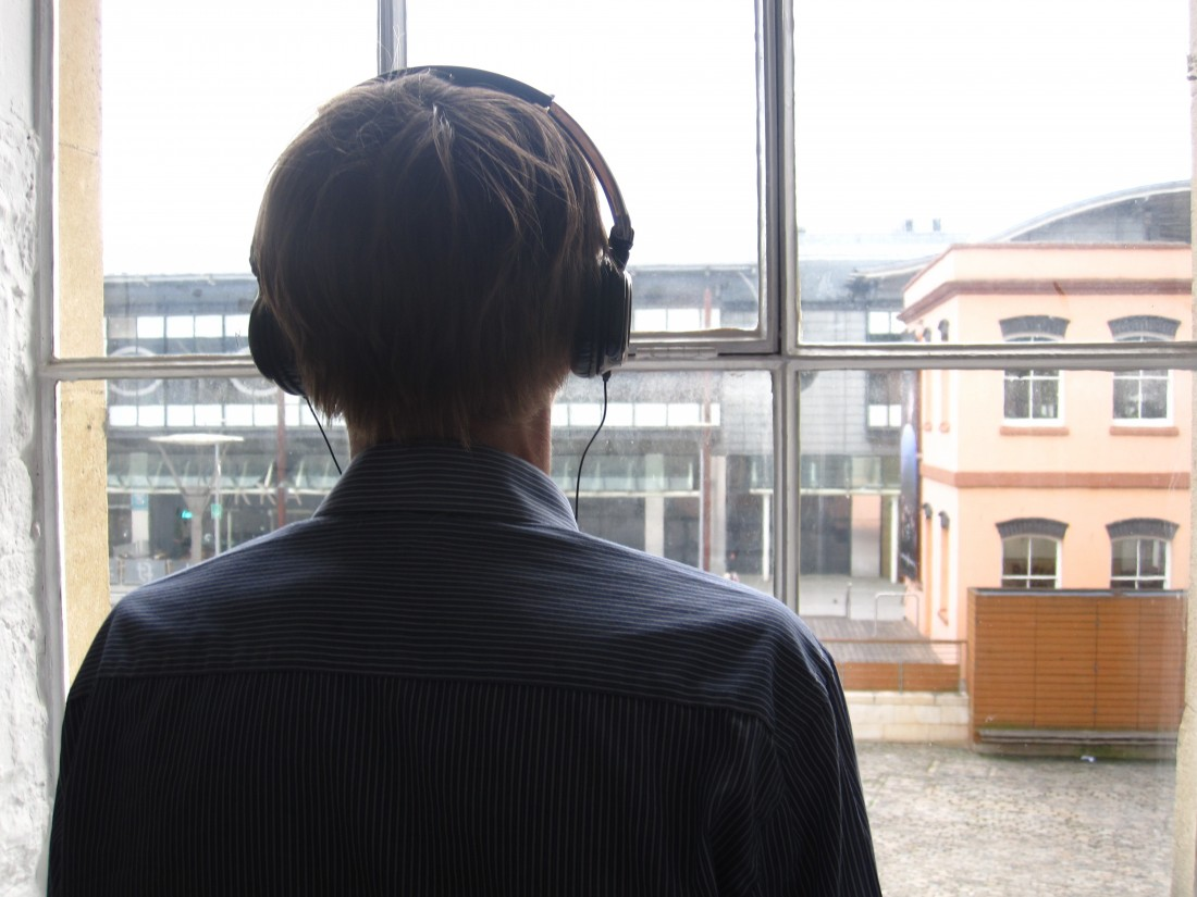 Proto-Type Theater: Fortnight.  The back of a man wearing headphones.