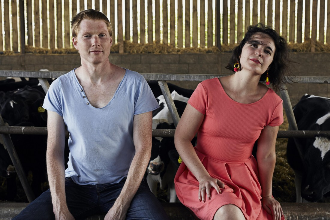 Kat and Alister from Two destination Language are sat in a farm in front of cows